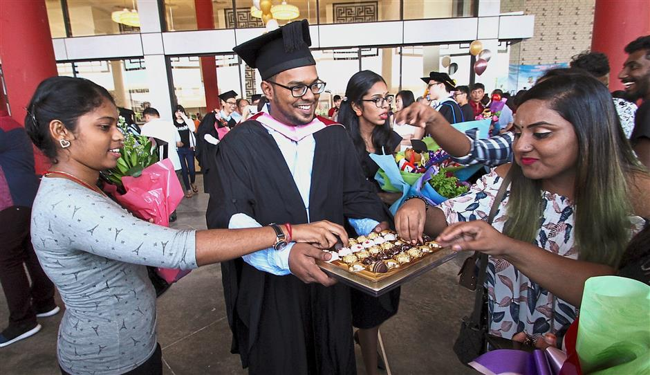 K. Logeshwaran (centre), who majored in advertising, offered his friends chocolates after the 26th Utar Convocation session in Kampar.