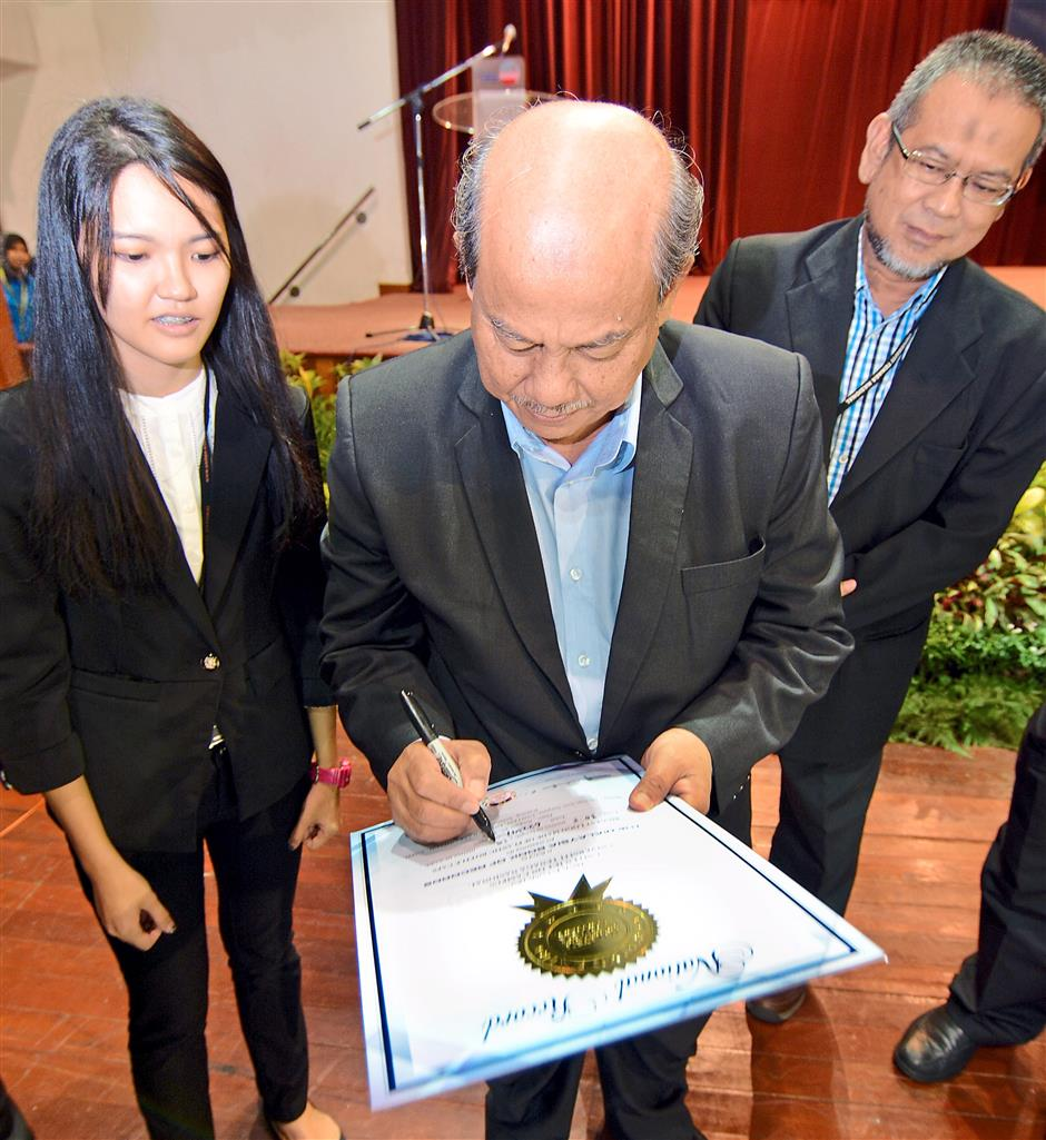 Ahmad Zaki (middle) noting down the students' record on a certificate while Chong (left) and Uniten College of Engineering deputy dean Associate Prof Dr Nasri A. Hamid look on.