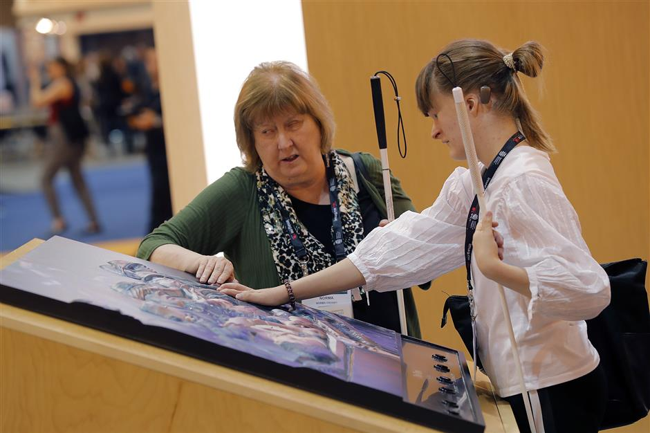 Norma Crosby, left, state president for the Texas chapter of the National Federation of the Blind, and Sophie Trist, a New Orleans chapter member, touch a bass relief of a photograph of the Vietnam Tet Offensive, by John Olson, whose company 3DPhotoworks also makes the bass relief, at the American Alliance of Museums Expo in New Orleans, Monday, May 20, 2019. It is one example of how museums are reaching out to make their collections more accessible, said Elizabeth Merritt, vice president for strategic foresight for the group, which represents museums of all sorts, from tiny community history museums to huge zoos. (AP Photo/Gerald Herbert)