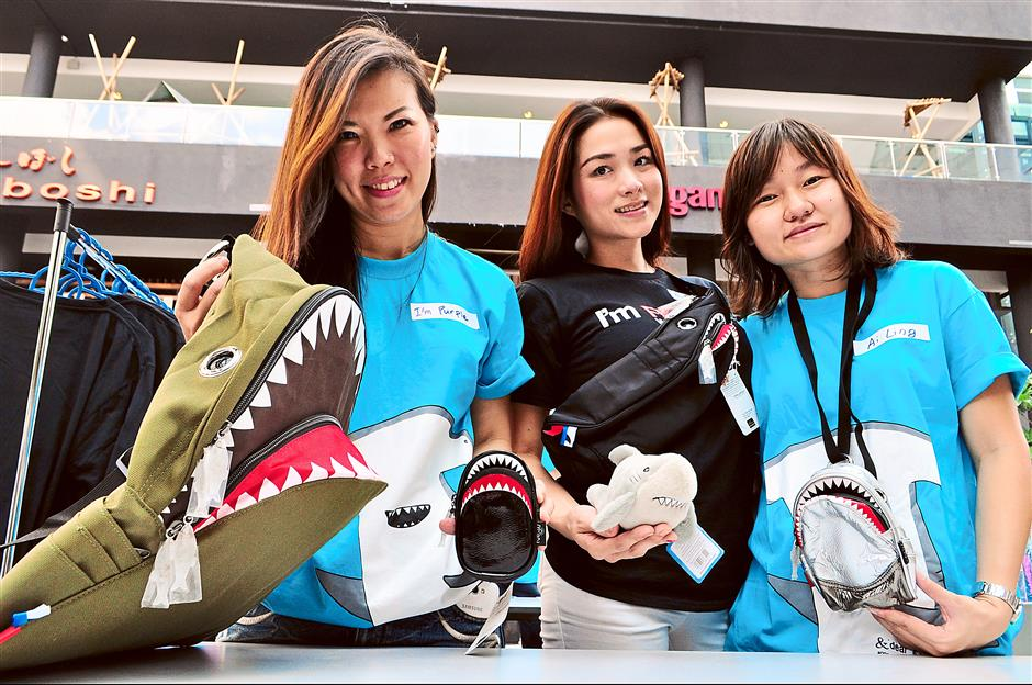 For the cause: (From left) Purple, Khoo and April displaying shark-themed merchandise on sale.
