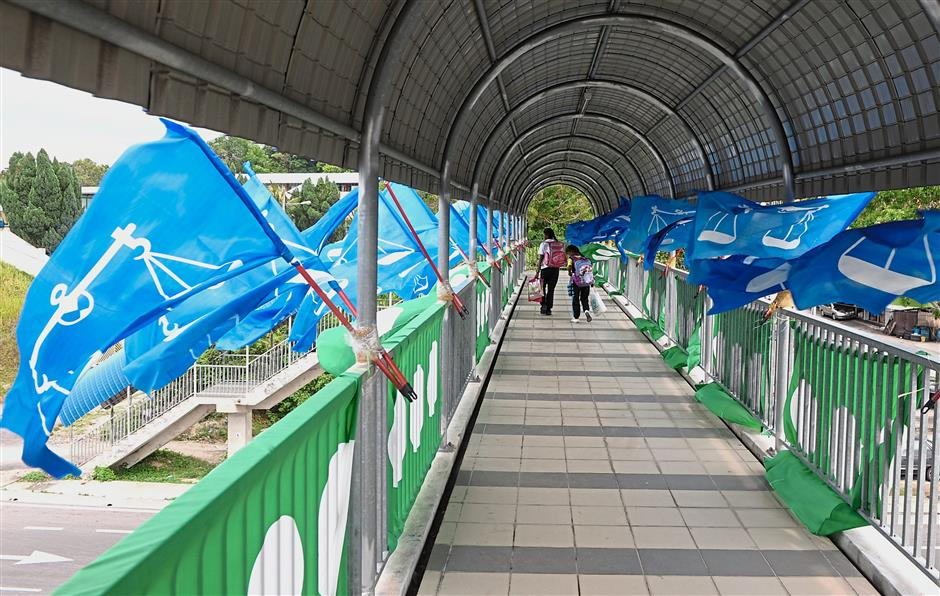 An overhead bridge in Jalan Batu Maung in Bayan Lepas is covered with Barisan and PAS flags while (right) Barisan and PKR flags flutter in the wind along Jalan Mayang Pasir. — ASRI ABDUL GHANI/The Star