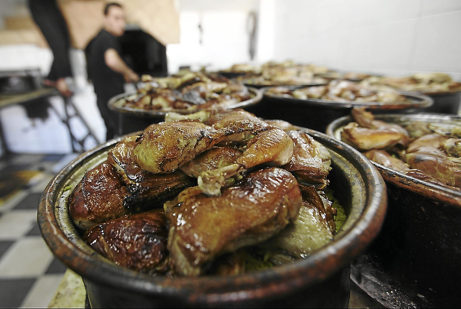 Aromatic dish: A Palestinian man prepares a traditional festive dish known as Qidra at a bakery before the Iftar meal in the West Bank city of Hebron. The dish, which dates back to the courts of Persia, contains rice and meat or chicken and is cooked in a wood-fired oven. In it, there is a standard mix of spices and abundant cloves of unpeeled garlic. - EPA