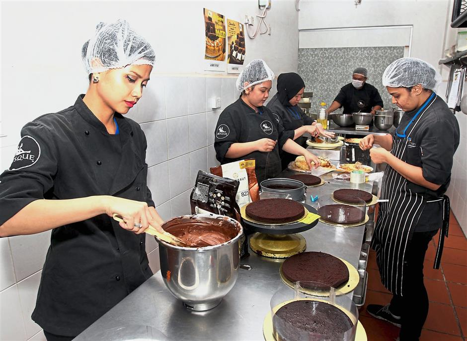 Kitchen elves: A young and energetic team making the cakes at its central kitchen in Damansara Perdana.