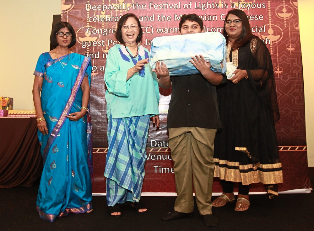 Maria (second from left) presenting a lucky draw prize to a young guest as MCC members S. Sivamalar (left) and Y. Jimetra look on.