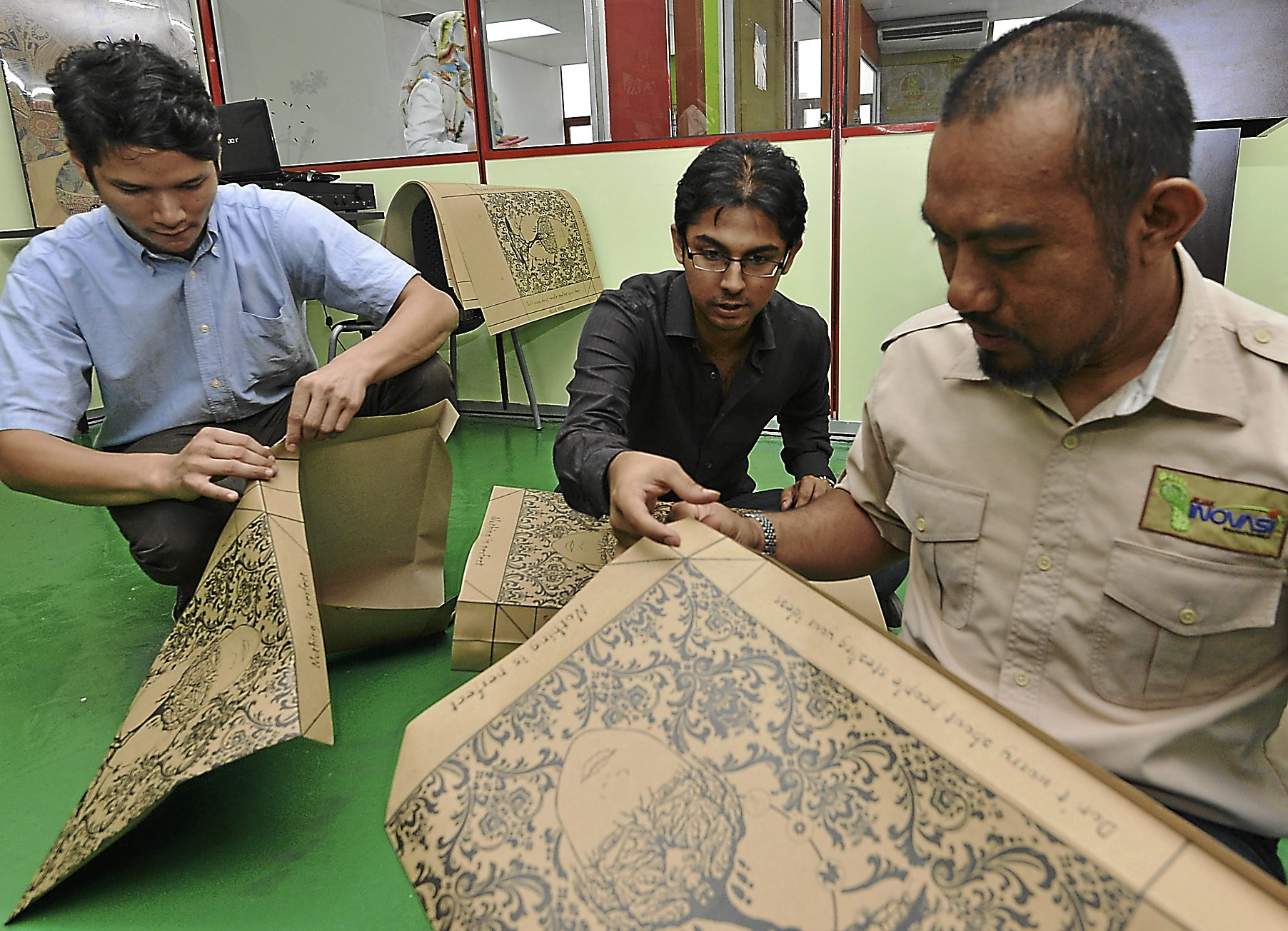 Biji-Biji Co-founder Azam Hisham (left) and Rashvin Pal Singh (middle ) showing YIM chief operating officer Muhammad Aziph Datuk Mustapha how to create a paper bag during the Donate Your Idea Workshop at  Skills Technical Innovation College, Kuala Lumpur on July 8.