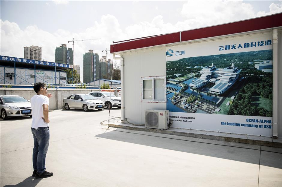 A man stands in front of a banner featuring an illustration of the new Oceanalpha Co. headquarters in Zhuhai, China, on Thursday, May 18, 2018. Oceanalpha, one of a handful of companies around the globe specializing in ocean-going drones that operate on the surface, has fired the interest of some of China's biggest venture capitalists. Photographer: Qilai Shen/Bloomberg