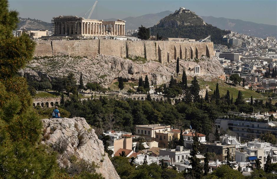 A tourist sits on March 18, 2019 at the Filopappou hill in Athens, underneath the Acropolis, an area which in 2016 was named Airbnb's fifth fastest growing neighbourhood globally with an 800-percent jump in home-sharing. - The Greek chamber of hotels commissioned a Grant Thornton study that found that over 76,000 properties in Greece are available on home-sharing platforms. The study argued that declining availability had pushed up rents in central Athens by 9.3 percent in a year, disproportionately affecting poorer sections such as pensioners and single-parent families. (Photo by LOUISA GOULIAMAKI / AFP)
