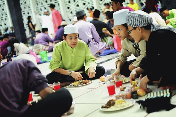 Communal affair: Boys share the spirit of the occasion as they break fast at the National Mosque.