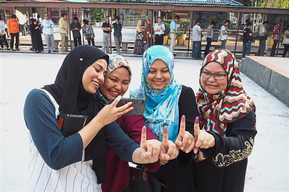 Zunaira (left) cast her vote with her sisters Nurul Farina (second from left) and Noor Hidayah Zakaria (right), and their neighbour Raihan Rahmat (third from left).