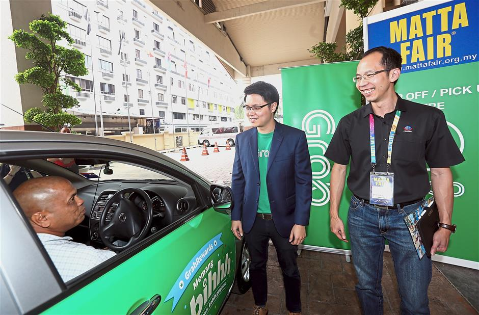 Grab business development head JJ Tan (centre) and MATTA honorary secretary-general Nigel Wong launching the Grab service at the fair.