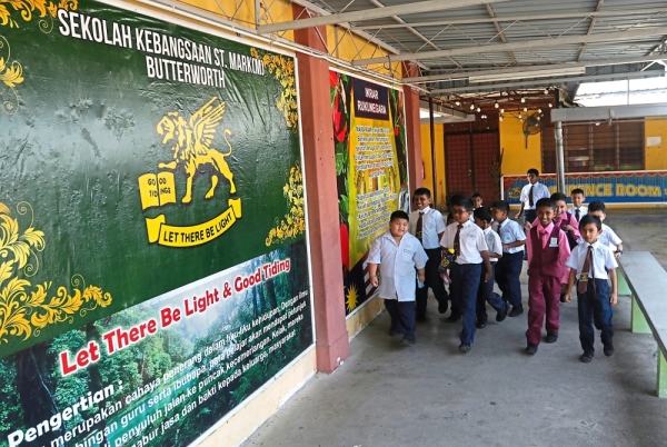 Pupils walking past posters bearing the Rukunegara and the school motto at SK St Mark (M) Butterworth in Jalan St Mark. — Photos: ZHAFARAN NASIB/The Star