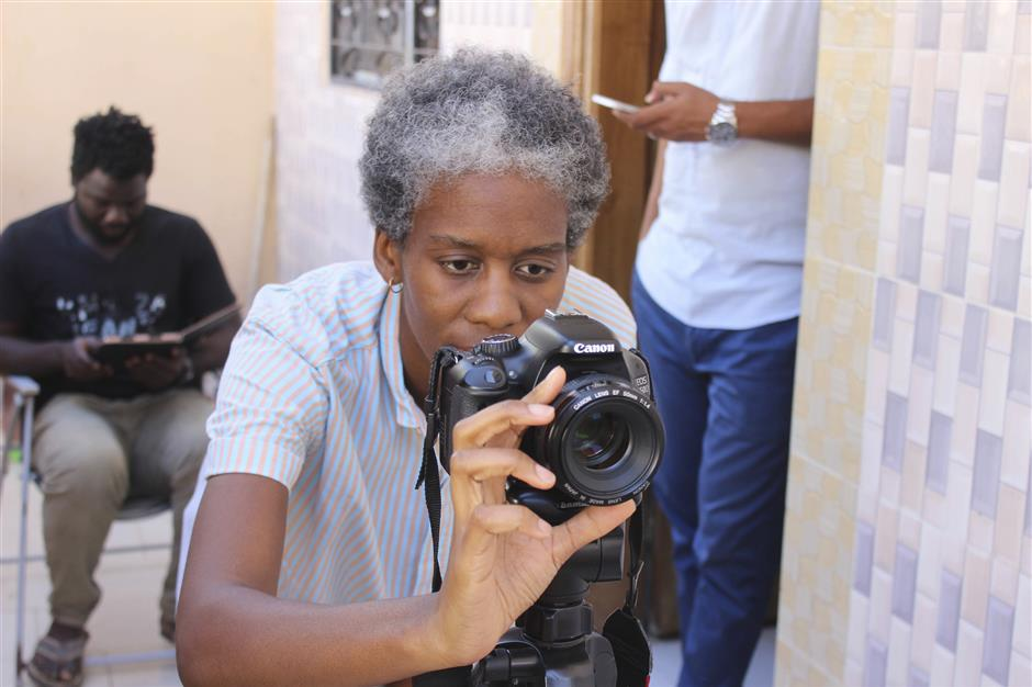 This Nov. 20, 2018, photo shows filmmaker Tuleka Prah, the founder of My African Food Map, at work in Ngaparou, Senegal. In the quiet hours before lunch, two women worked side by side in an airy kitchen. One, a chef, cleaned fresh red snapper filets with a sharp knife. The other, a filmmaker, pointed her camera into a large pot of simmering vegetables. (AP Photo/Amelia Nierenberg)