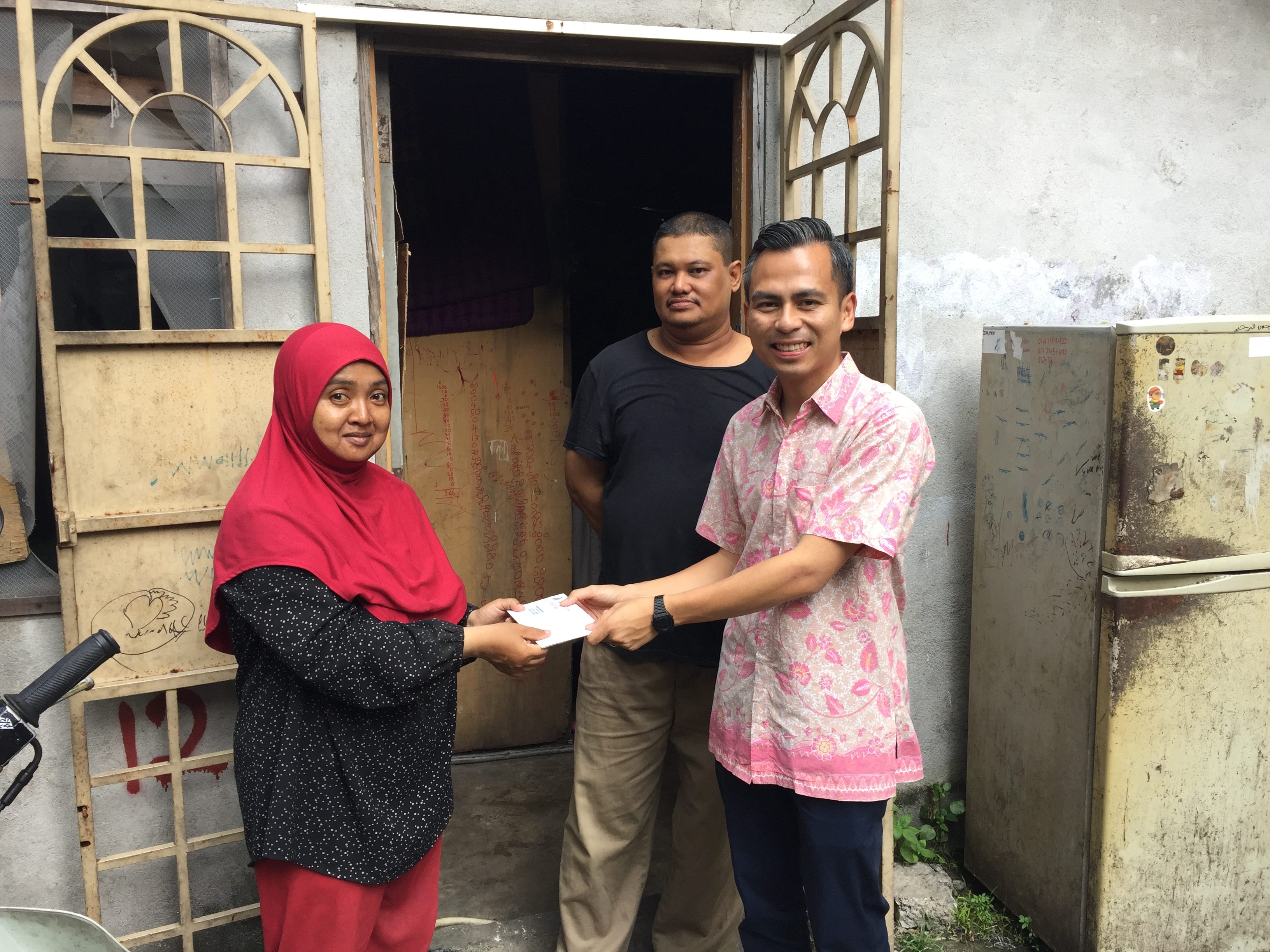 (right) Lembah Pantai MP Fahmi Fadzil handing over the offer letter to (left) Farizah Ibrahim while her husband (middle) Shahdi Abdullah looks on.