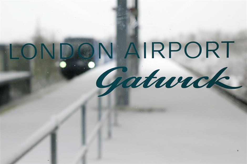 FILE - In this Dec. 1, 2010, file photo, a terminal link train arrives behind a glass window at the snow covered terminal station at London\'s Gatwick Airport in Horley, England. London\'s Gatwick Airport shut down late Wednesday, Dec. 19, 2018, while officials urgently investigated reports that two drones were flying above the airfield. (AP Photo/Sang Tan, File)