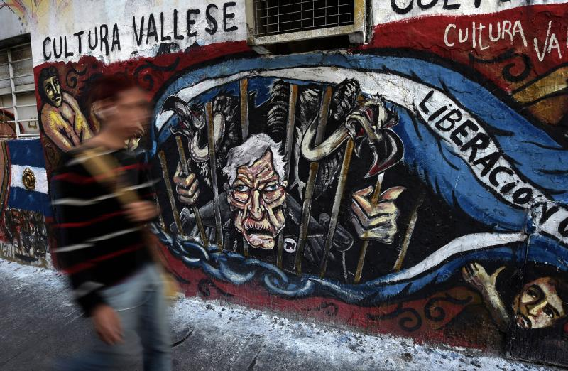 A man walks next to a grafitti depicting US\' Judge Thomas Griesa and vultures behind bars, outside the National Congress as lawmakers discuss the approval of a bill on sovereign payment of debt that would skirt US restrictions in Buenos Aires on Sept 10, 2014. The bill has been approved - AFP Photo.