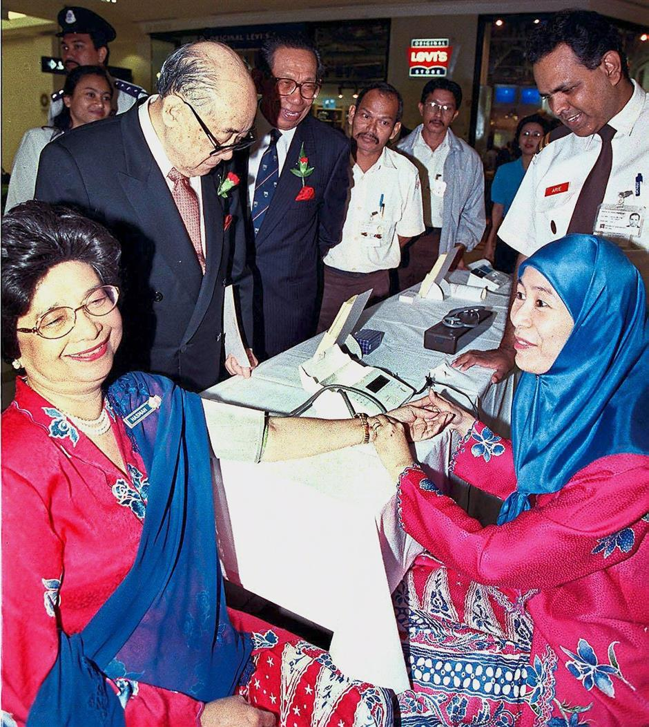 """Always professional: Dr Wan Azizah checking Tun Dr Siti Hasmah's blood pressure during the """"Heart Week Campaign"""" at Suria KLCC in 1998."""