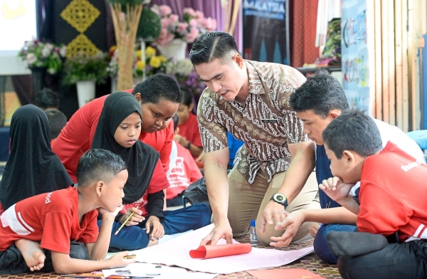 Cikgu AG (in brown batik) guiding his pupils to make Teachers' Day cards to present to their teachers.