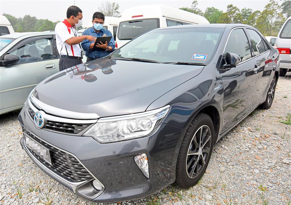 Checking the numbers: SPAD officers conducting an inventory inspection of seized private cars at the commision's vehicle impound facility. — P NATHAN/ The Star