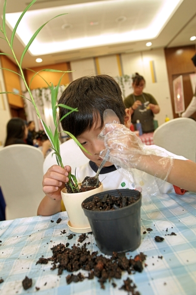 A young visitor learning to plant the Arundina at a DIY workshop held during the preview event at Setia Eco Park Sales Gallery in Shah Alam.
