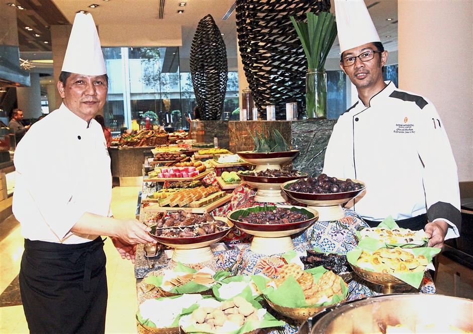 Ghazali (right) and junior sous chef Aimilan Zainal Abidin with a spread of the Ramadan dishes. — M. AZHAR ARIF/The Star