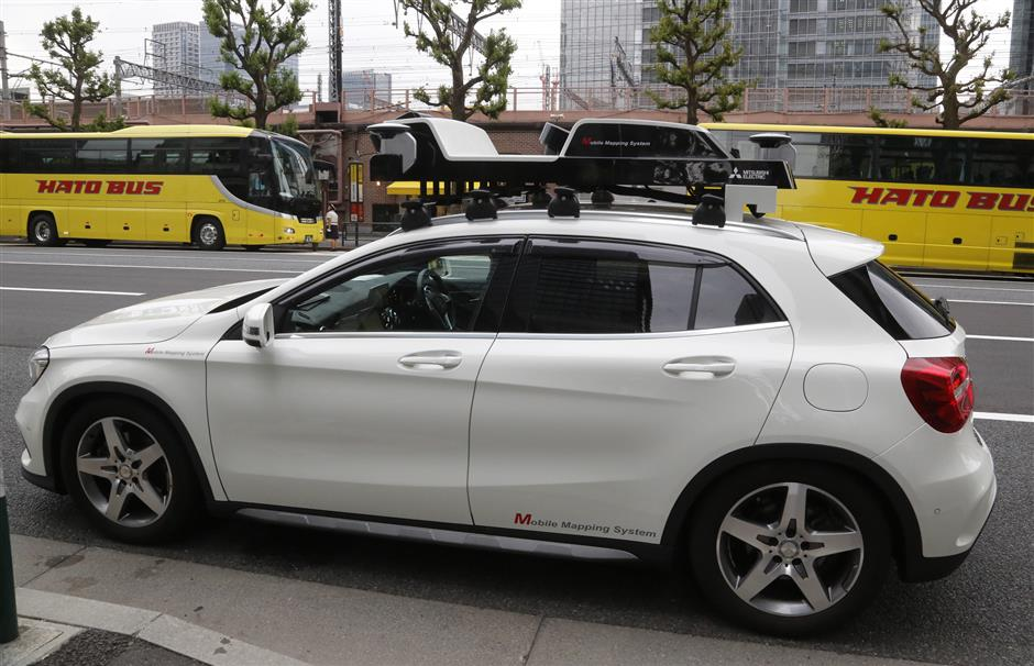 In this May 31, 2018, photo, a car is equipped with sensors to create 3D digital mapping in Tokyo. Technology companies are racing to develop ultra-precise three-dimensional digital maps that can guide self-driving cars to within inches of where they are supposed to be _ a hurdle the industry needs to clear if it hopes to deliver on its promise of widespread use of driverless vehicles. (AP Photo/Yuri Kageyama)