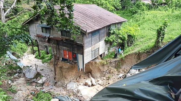 Dangert zone: A JKR personel inspecting the cave-in in Jalan Lembah Permai and (inset) the abandon squarter house. — ZAINUDIN AHAD/The Star