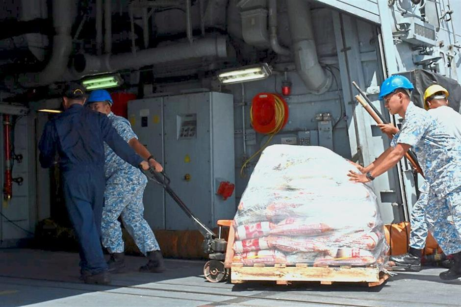 Navy personnel loading Malaysian navy ship KD Kedah that is now on its way to Zamboanga City in southern Philippines to help victims of Typhoon Tembin.