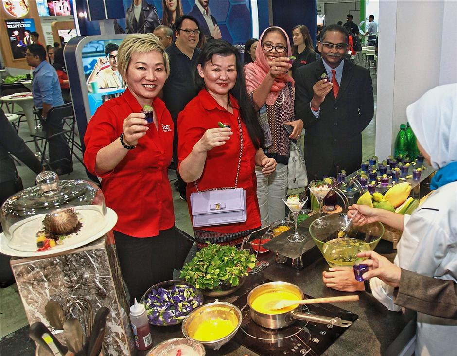 (From left) Law, Ng, Dr Siti Hamisah and Education Ministry corporate communications head Dr G. Manimaran taste the galaxy lemonade mocktail at the Quest International University Perak booth.