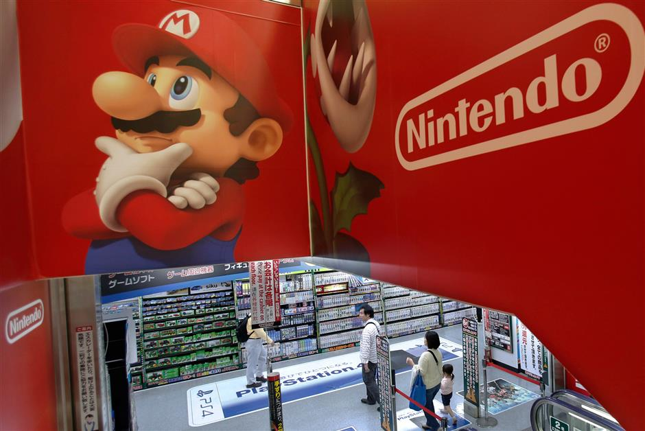 FILE - In this May 7, 2014, file photo, shoppers walk under the logo of Nintendo and Super Mario characters at an electronics store in Tokyo. Nintendo Co. is reporting solid sales and profit for the fiscal fourth quarter, powered by brisk demand for its Switch machines. The Japanese maker of Super Mario and Pokemon games reported Thursday, April 26, 2018,  that its January-March profit totaled 4.4 billion yen ($40 million), reversing a 394 million yen loss it racked up the previous year. (AP Photo/Shizuo Kambayashi, File)