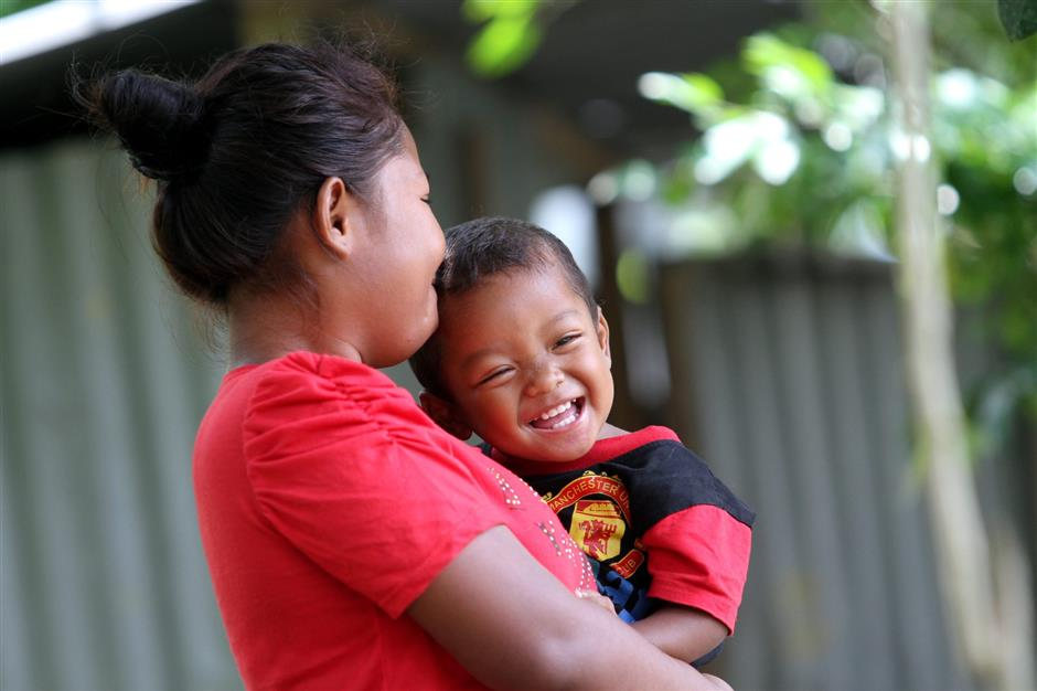 An Orang Asli and her child having some playtime during the Star Publications Good Day Out in-house-project where volunteers from the public have come together to help Orang Asli families refurbish their homes (September 14, 2013).