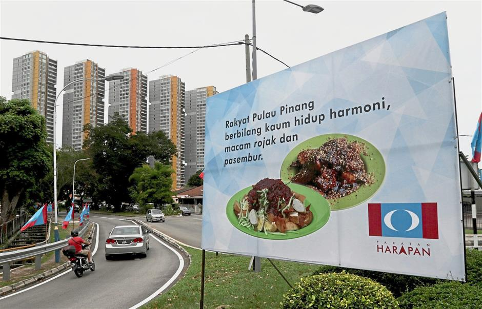 Billboards put up by Pakatan Harapan coalition of local street foods such as rojak, pasembur and nasi lemak (inset) with statements to garner support from voters for the 14th general election in George Town, Penang. — ZHAFARAN NASIB/The Star