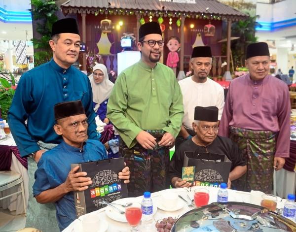 Zahrin (standing second from left) and UDA's senior executives hosting senior citizens from Rumah Seri Kenangan Kampung Ungku Mohsin Johor Baru at the company's Hari Raya Aidilfitri open house.
