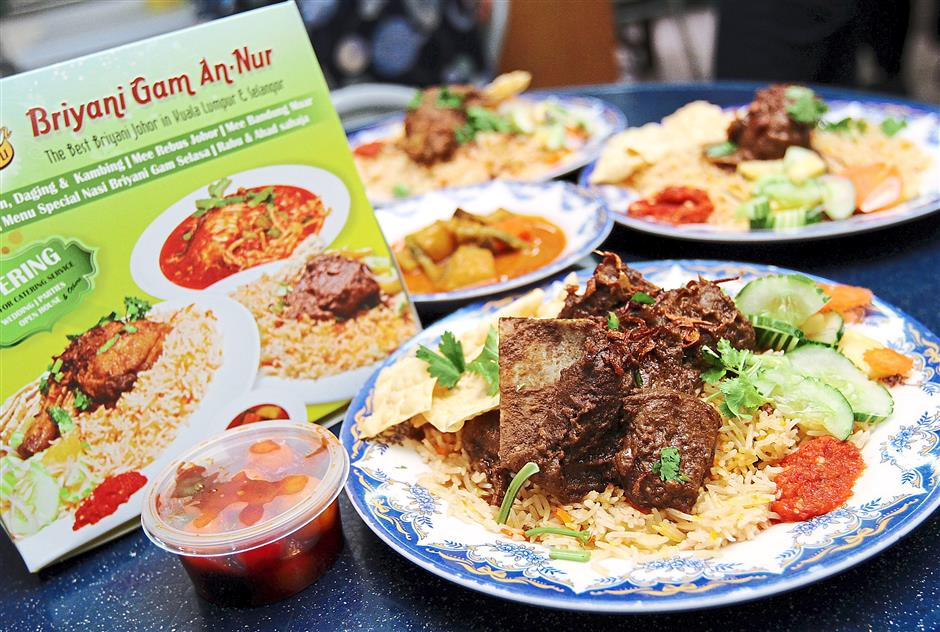Kicker: Pictured in front is Nasi Briyani Gam An-Nur's nasi briyani kambing. They also serve the meal with a choice of chicken and beef.