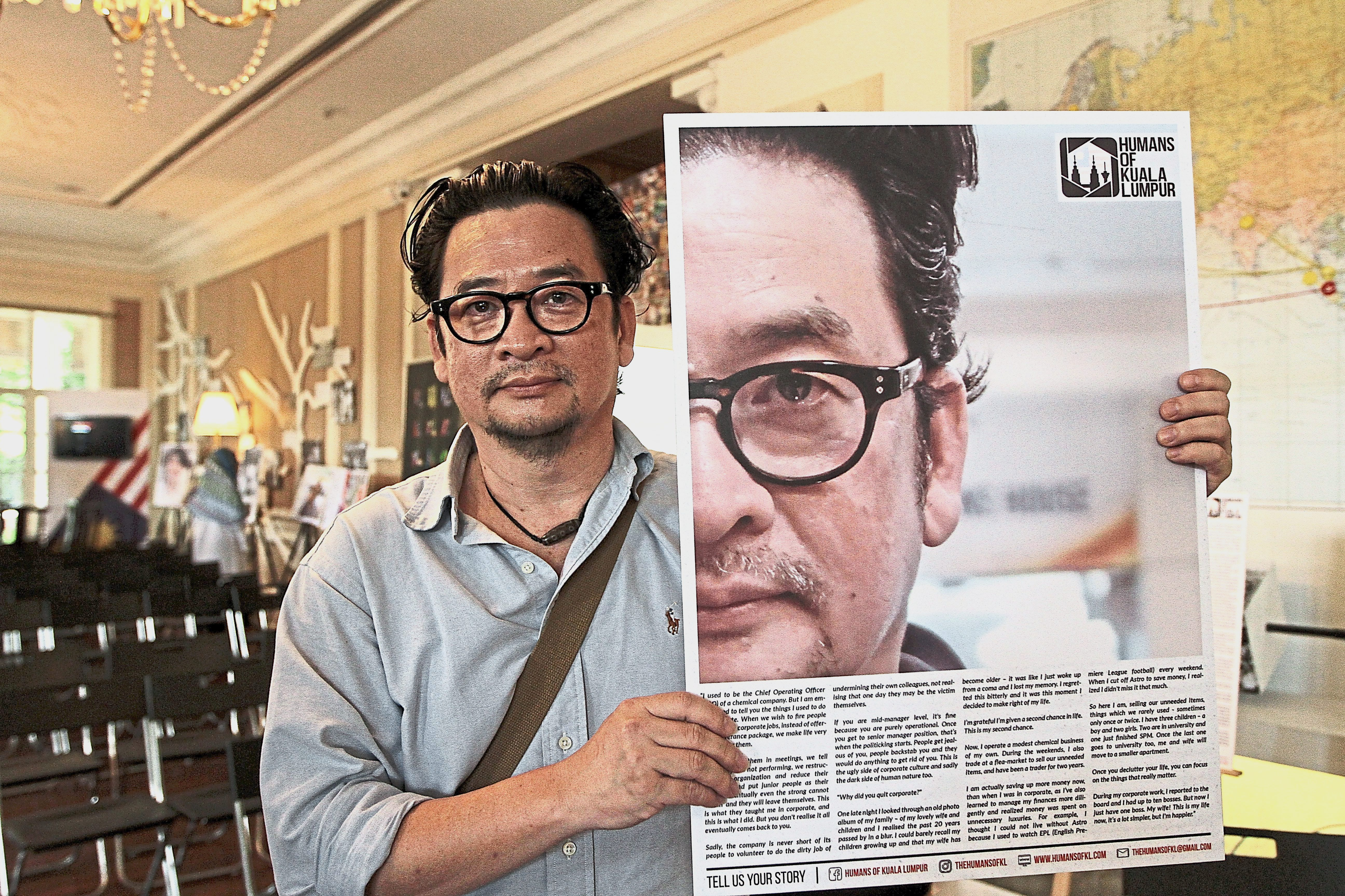Ding showing his photo story at the exhibition.