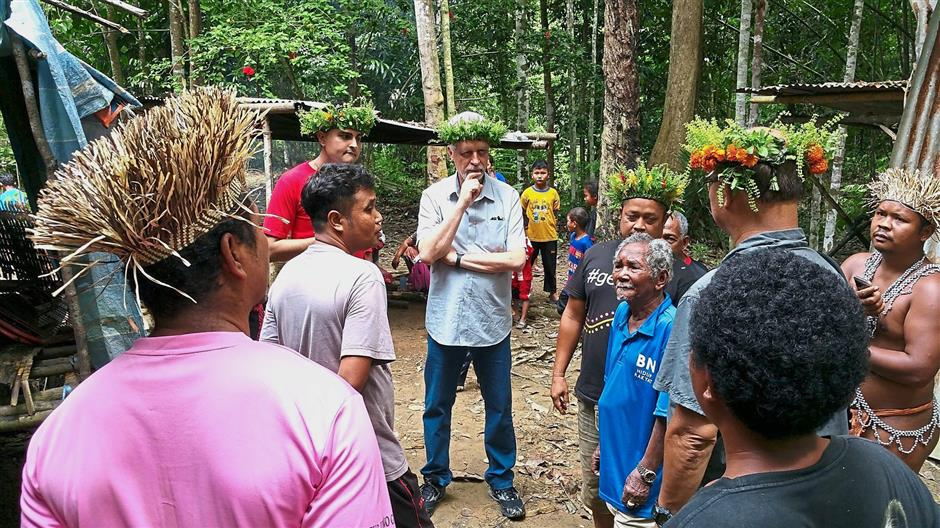 Getting it from the source: Heller (middle) in Gua Musang, learning from the orang asli about the way they live, including their water woes and sanitation problems.