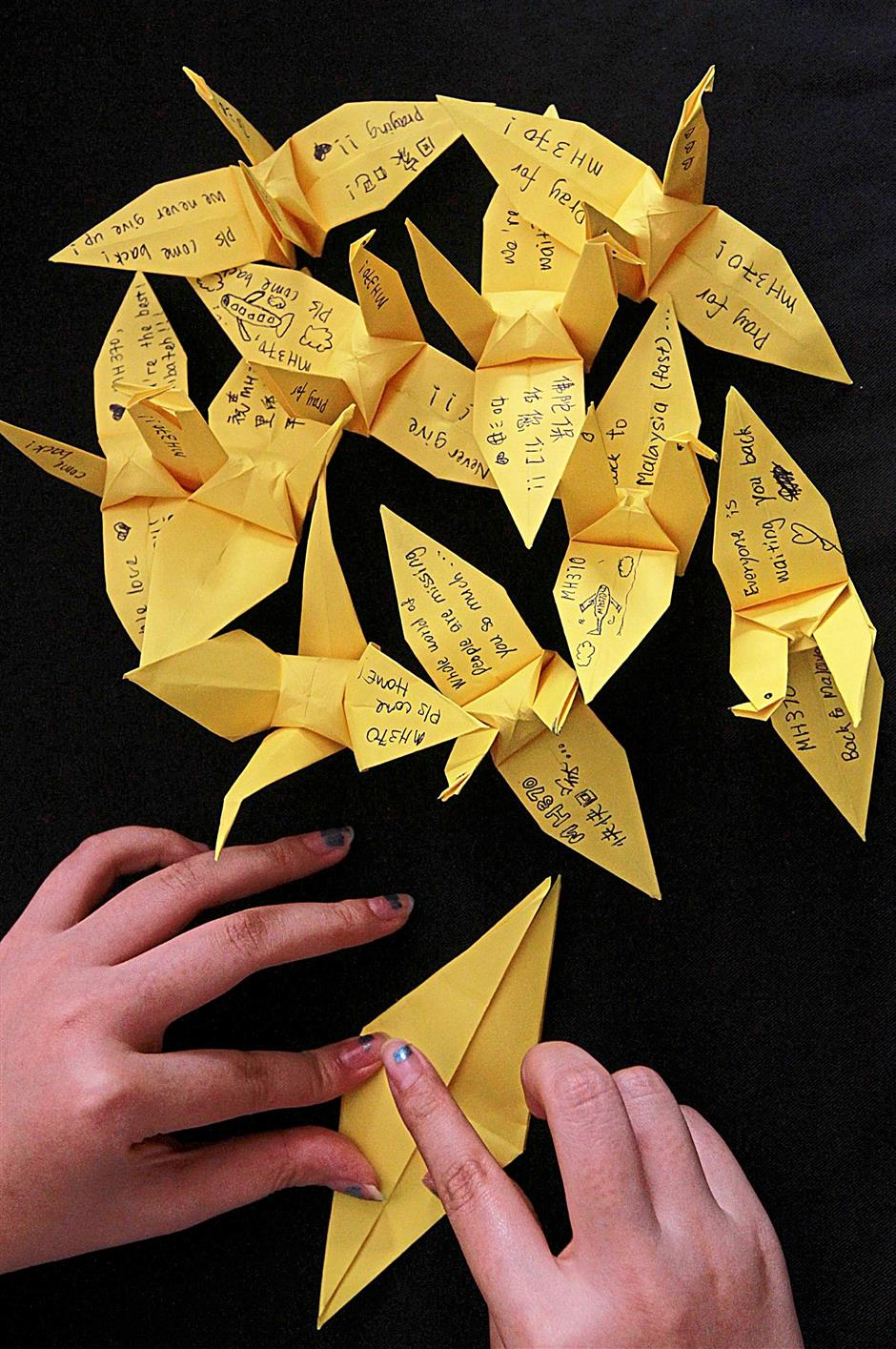 1. Participants channelling their prayers for the missing airliner through the act of folding paper cranes in various colours.2. Well wishes are inscribed on the wings of the paper cranes.