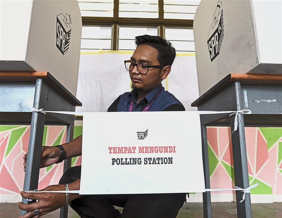 Final touches: Election Commission official Ridza Asyraf Nor Mizam preparing voting booths at a school in Panchor, Muar. u2014 Bernama