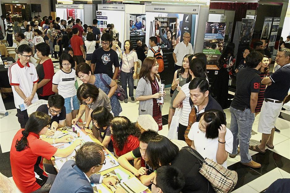 Visitors shopping for courses at the fair held at Convention 33, Prangin Mall, Penang. — Photos: GOH GAIK LEE and CHAN BOON KAI/The Star