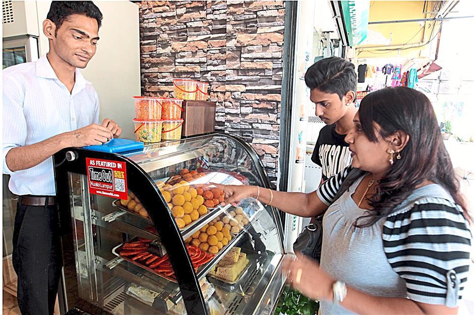 (right) Sivagami Arjunan, 40, choosing sweets from Jesal Sweet House in Brickfields, while her son Teeban Sarma Nandakumaran, 18,  looks on.