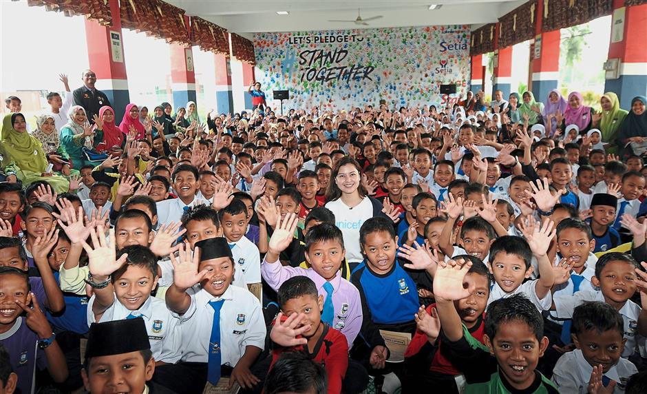 """Lisa (standing in the middle) with the pupils from SK Kota Dalam in Ayer Hitam, which were among the winners of the StandTogether """"kindness project"""" competition."""