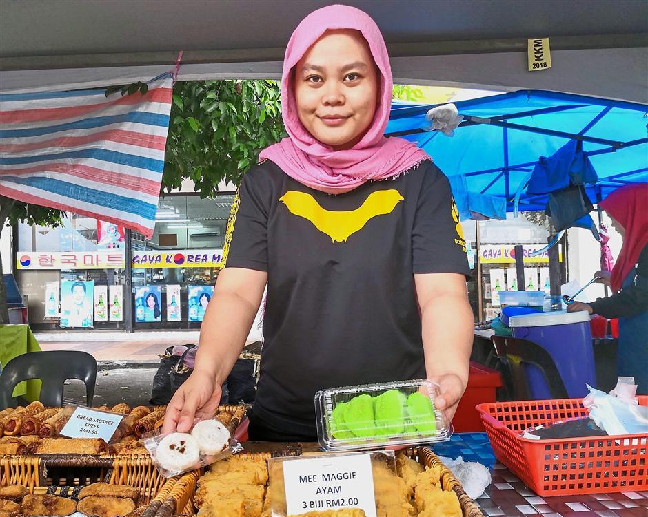 Brisk business: Zanariah showing the hot-selling snacks at her stall at the Asia City Ramadan bazaar in Kota Kinabalu.