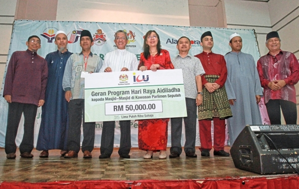 (Above) Kok (centre) with mosque representatives during the presentation of RM50,000 to five mosques in the Seputeh area.