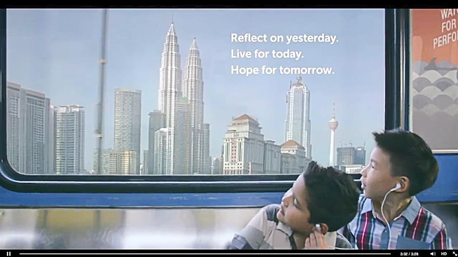 Blast from the past: A screen grab of a scene from the Petronas Merdeka video advertisement of two friends seeing Malaysia grow.