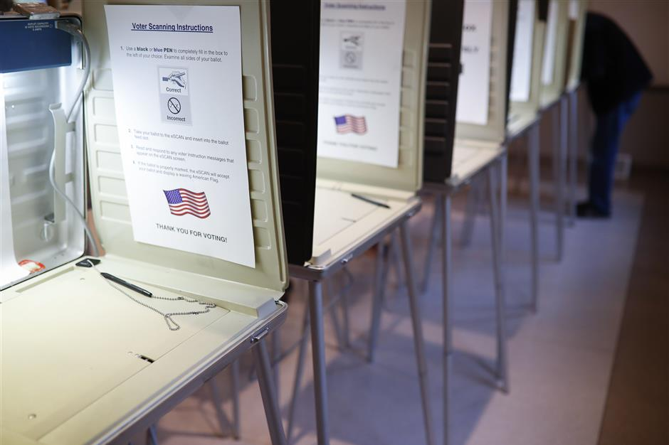 FILE- In this Nov. 8, 2016, file photo a lone voter fills out a ballot alongside a row of empty booths at a polling station in the Terrace Park Community Building on Election Day in Cincinnati. Microsoft announced Monday, May 6, 2019, an ambitious effort to make voting secure, verifiable and reliably auditable with open-source software that top U.S elections vendors say they will explore incorporating into new and existing voting equipment. (AP Photo/John Minchillo, File)