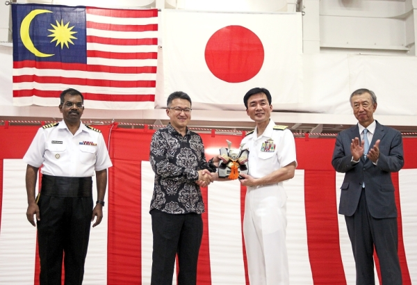 Liew (in batik) receiving a memento from Rear Admiral Egawa at the welcoming reception on board JMSDF's helicopter-carrier destroyer JS Izumo at the Boustead Cruise Centre Terminal as Miyagawa (right) and Capt Saravanan look on. — GLENN GUAN/The Star