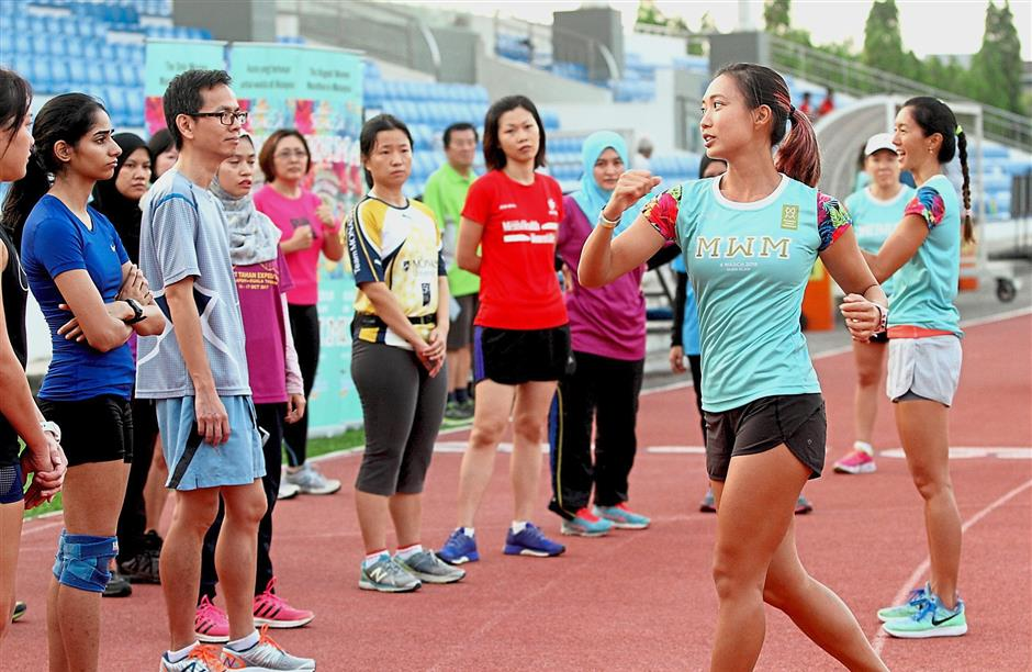 Personal trainers Siah (left) and Teoh sharing tips with participants during a running clinic by Malaysia Women Marathon.