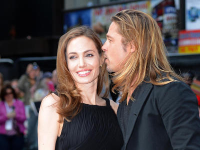 """US actress and humanitarian campaigner Angelina Jolie (left) poses with her US actor and fiance Brad Pitt (right) as she arrives for the UK premiere of Brad Pitt\'s latest film """"World War Z"""" in Leicester Square in central London on June 2, 2013. - AFP PHOTO / LEON NEAL"""