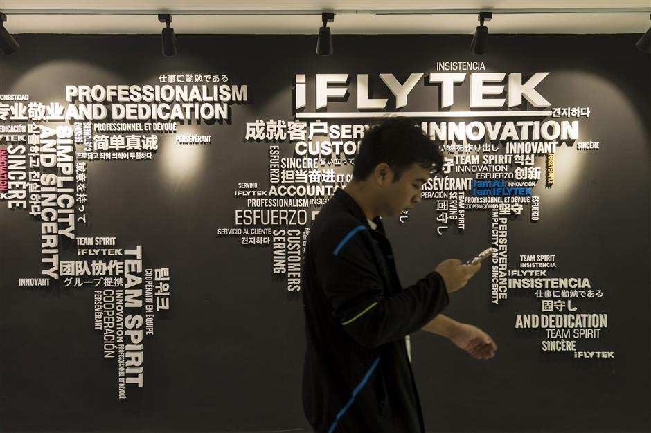 An employee walks past a wall display inside Iflytek Co.\'s regional headquarters in Guangzhou, China, on Tuesday, Oct. 31, 2017. Iflytek, which specializes in voice recognition, is collaborating withu00a0Guangzhou Pharmaceutical Holdings Ltd. on a network of health centers that will rely partly on artificial intelligence for diagnosis and treatment. Photographer: Qilai Shen/Bloomberg