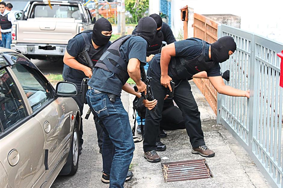 Fighting terrorism: Bukit Aman Special Branch Counter Terrorism Division personnel preparing to raid a house in this file photo.