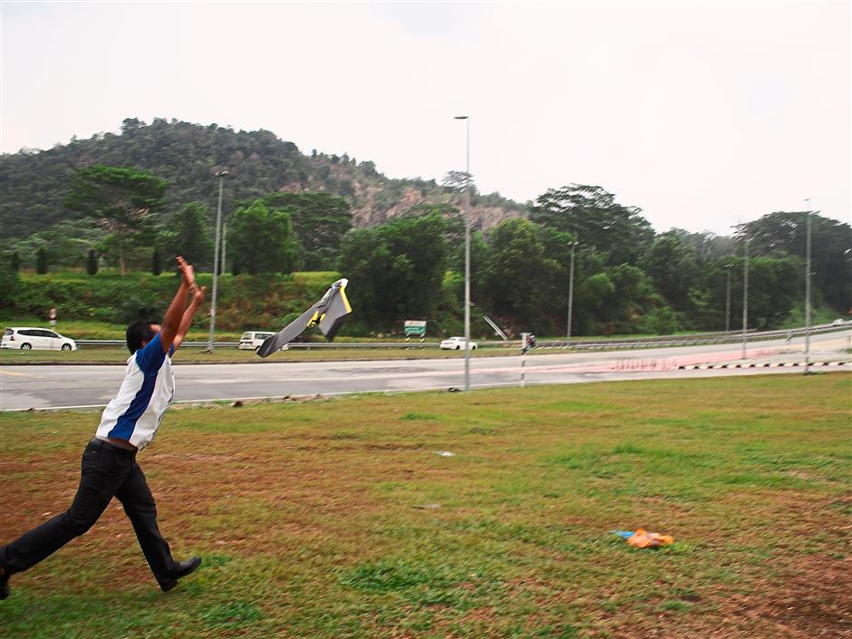 One of the staff launching the UAV as part of their mapping activities in an open area to avoid collision with buildings or trees.